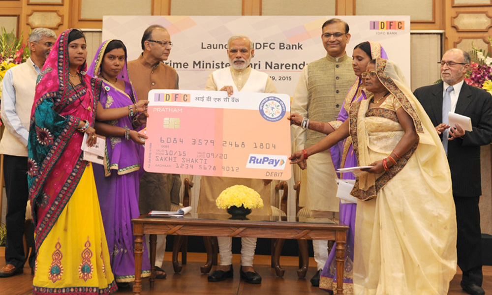 Delhi, 20 Oct 2015:  PM Narendra Modi distributing RuPay Cards under PMJDY by the IDFC Bank to the beneficiaries, at the launch of the IDFC Bank.