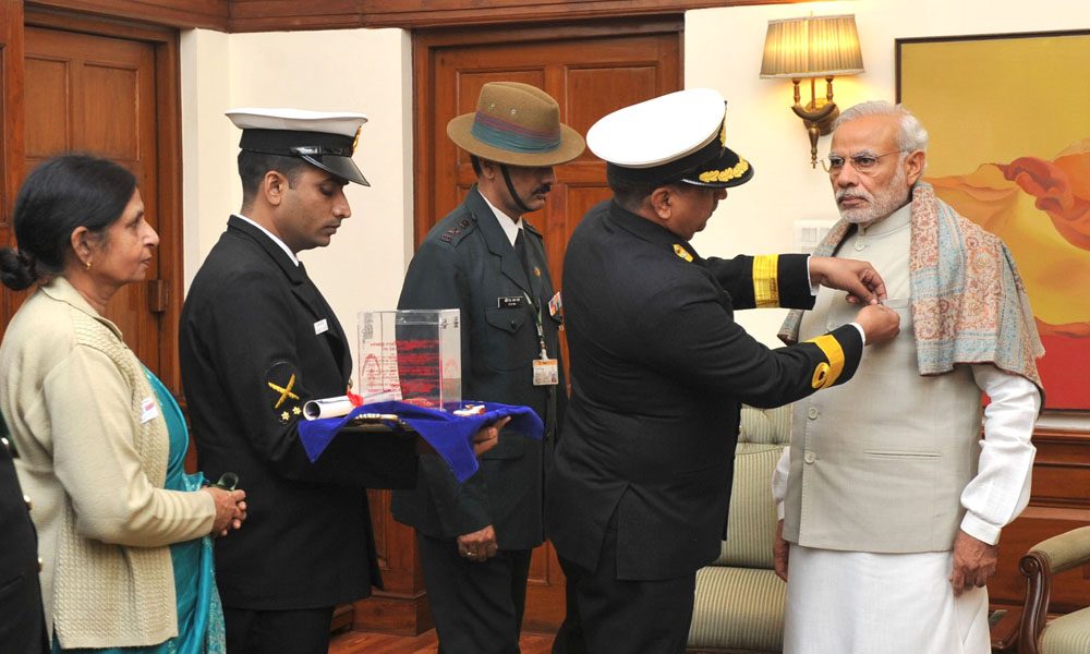 Delhi: 8 Dec 2015: Officers of the Kendriya Sainik Board pinning a flag on the PM Narendra Modi, on the occasion of Armed Forces Flag Day.