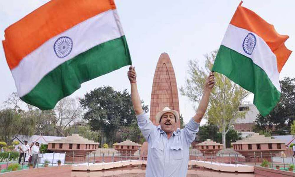 Punjab,13th April 2016: An indian man dressed as the freedom fighter bhagat singh waves indian national flag on the 96th anniversary of the jalianwala bagh.