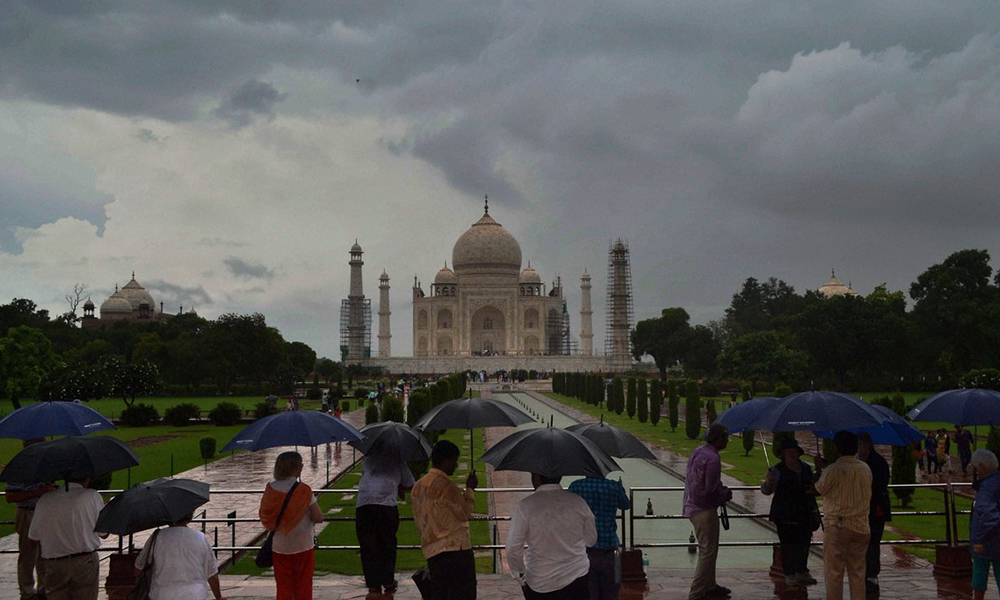 Uttar Pradesh, 1st Sept 2016: Visitors with umbrellas during rains at Taj Mahal in Agra.