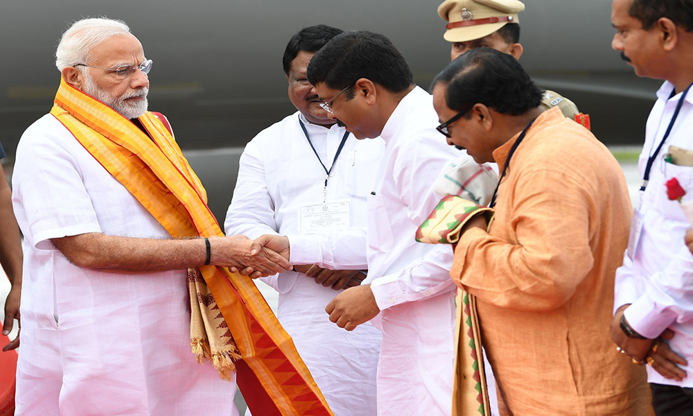 The Prime Minister, Narendra Modi being welcomed by the Union Minister for Tribal Affairs, Jual Oram and the Union Minister for Petroleum & Natural Gas and Skill Development & Entrepreneurship, Dharmendra Pradhan, on his arrival, at Bhubaneswar, in Odisha