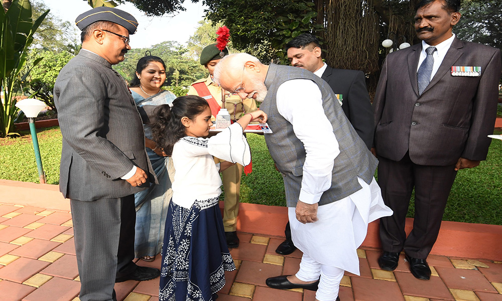 A little girl pinning flag on the Prime Minister, Narendra Modi, on occasion of the Armed Forces Flag Day, in Pune.