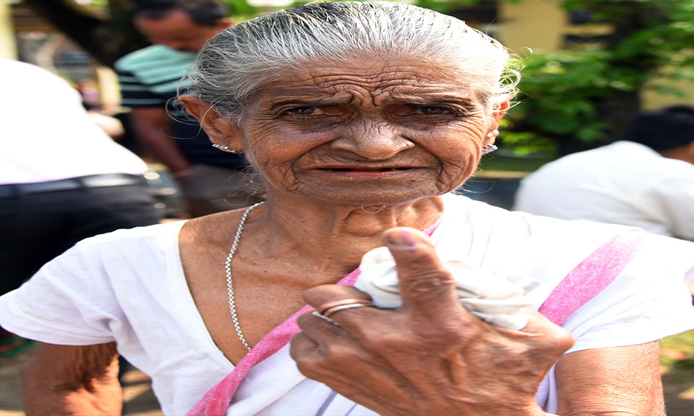 An elderly woman voter showing mark of indelible ink after casting her vote, at a polling booth, during the 2nd Phase of General Elections-2019, at Mangaldoi, in Assam.