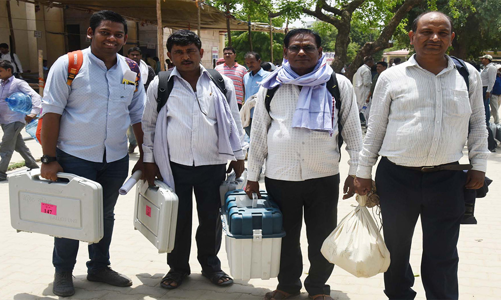 Polling officials carrying the Electronic Voting Machine (EVMs) and other necessary inputs required for the General Elections-2019, at the distribution centre, at Varanasi, Uttar Pradesh.